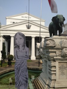 Flat traveler in front of elephant statue outside the National Museum